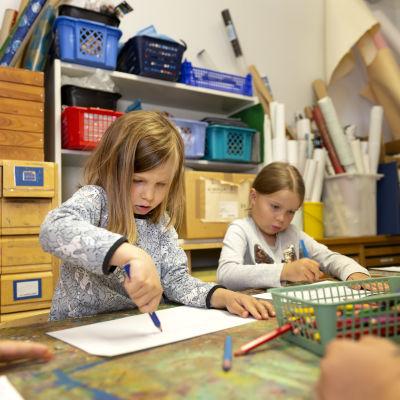 Lapset piirtää keskittyneesti piirustuksiaaan.