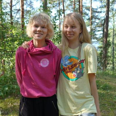 Ungdomarna Ada Willför och Beda Bergsröm står leende i en grön skog. Beda har armen om Adas axel.