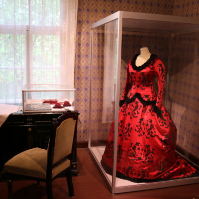 Museossa pöytä, tuoli sekä lasivitriinissä punainen juhlapuku.