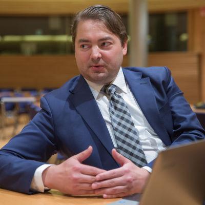 Riksdagsledamoten Ville Vähämäki sitter vid ett bord.