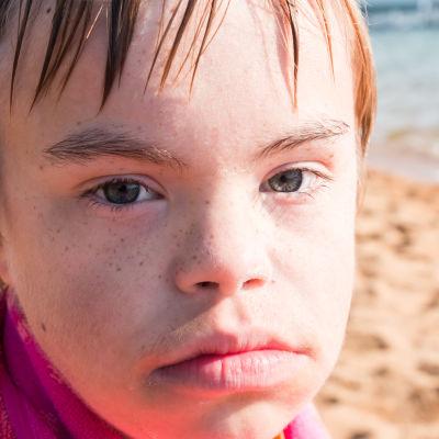 Ung pojke insvept i handduk tittar allvarlig tin i kameran