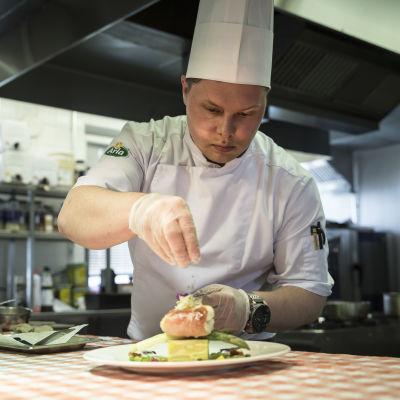 En kock lägger sista handen vid en matportion.