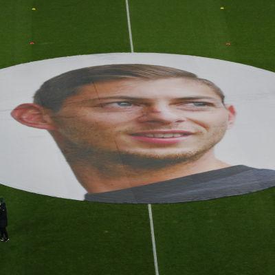 En stor duk med en bild på Emiliano Sala liggandes på en fotbollsplan.