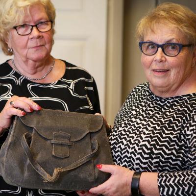Aira Hellström och Marja-Leena Suvitie, två damer med glasögon, håller i en större, brun handväska.