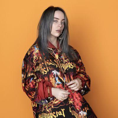 Laulaja Billie Eilish seisoo oranssia taustaa vasten.