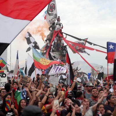 Flera människor håller upp flaggor under demonstration i Santiago i Chile.