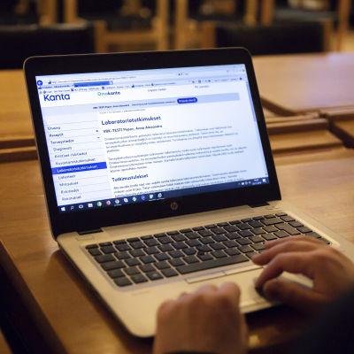 Olanyli kuva naisesta joka selaa tietokoneella Kelan Omakanta palvelua.
