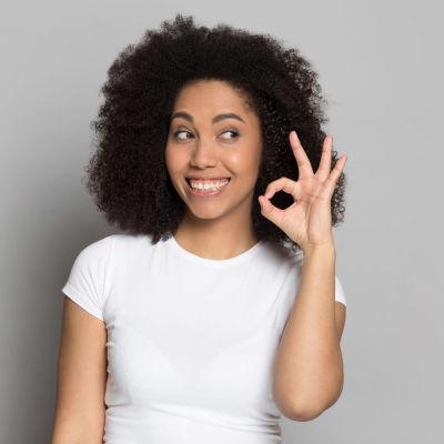 En kvinna ler stort och kniper samman tummen och pekfingret i en gest som betyder ok.