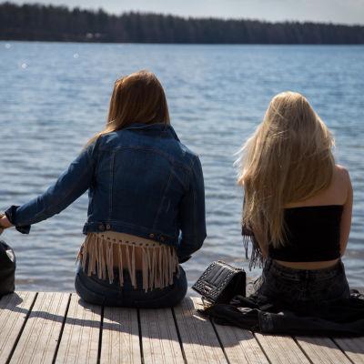 Kaksi anonyymiä nuorta aikuista naista istuu laiturilla järven rannalla keväällä.