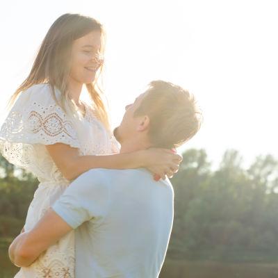 Man i kortärad skjorta lyfter upp leende kvinna i sommarklänning