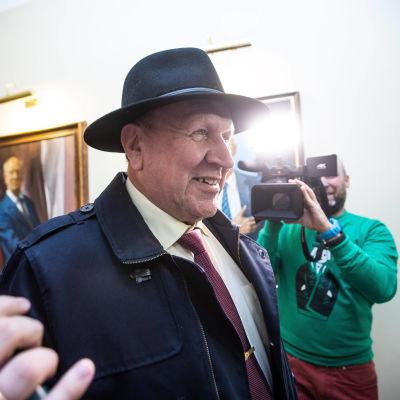 En äldre man i hatt blir fotograferad och har mikrofoner framför sig.