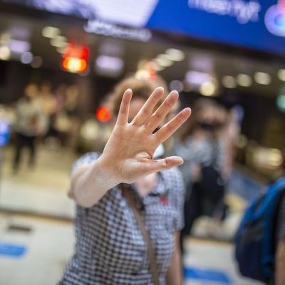 Kuvattava suojaa henkilöllisyyttään kameran eteen nostetulla kädellä Asematunnelissa.