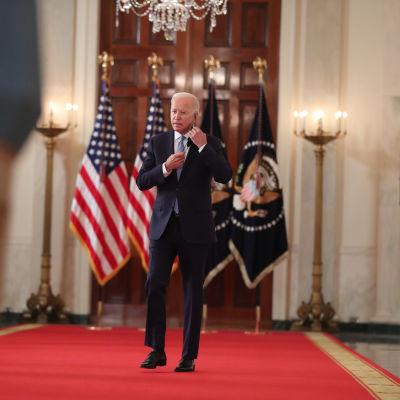 USA:s president Joe Biden tar av sig sitt munskydd inför ett tal i Vita huset.