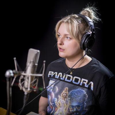 Jenni Poikelus Lukee kirjaa studiossa.