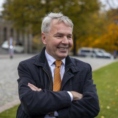 Minister Pekka Haavisto står framför riksdagshuset och ser väldigt glad ut.