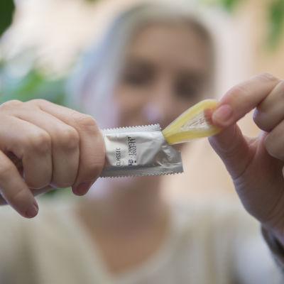 En person öppnar ett kondompaket.