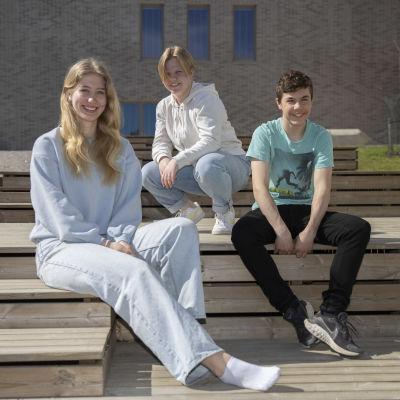 Tre högstadieelever sitter utanför en skolbyggnad i vårsolen och ler mot kameran.