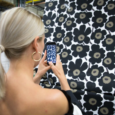 En kvinna fotograferar en blommig vägg med sin telefon.