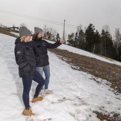 Två personer ser på en halvsnöig backe. En av kvinnorna pekar neråt mot någonting som inte ryms med på bilden.