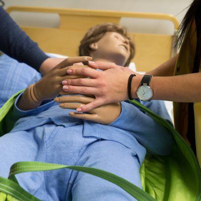 Kaksi lähihoitajaopiskelijaa laittaa potilasnukelle nostosidettä. Toinen pitää nuken käsistä kiinni.