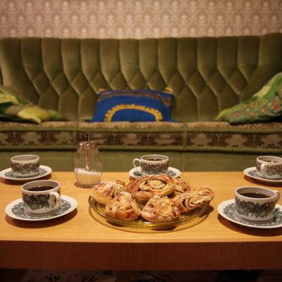 Ylen Vaalisohvan pääkuva. Kuvassa vihreän plyysisohvan edessä on olohuoneen pöytä. Pöydällä viisi kahvikuppia ja iso lautanen täynnä korvapuusteja.