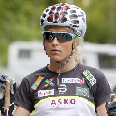 Therese Johaug ser fundersam ut med hjälm på huvudet och stavar i händerna.
