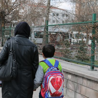 Nainen ja poika kävelevät selin kameraan.