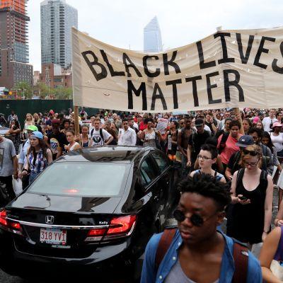 """Mielenosoittajia kadulla, """"Black lives matter"""" -kyltti"""