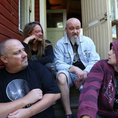 Bändin jäsenet istumassa treenikämpän portailla.