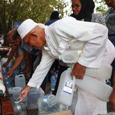 Invånare i Kapstaden, som lider av vattenbrist, fyller vattensflaskor med vatten från en bergskälla