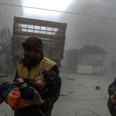 Biståndsarbetare hjälper ett skadat barn efter att Douma i östra Ghouta bombats.