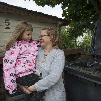 Saija Helin on nostanut tyttärensä Helmi Helinin katsomaan, mitä roska-astian eri lokeroihin on lajiteltu.