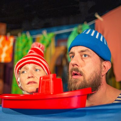 Två skådespelare lutar sina huvuden på en platsbåt.
