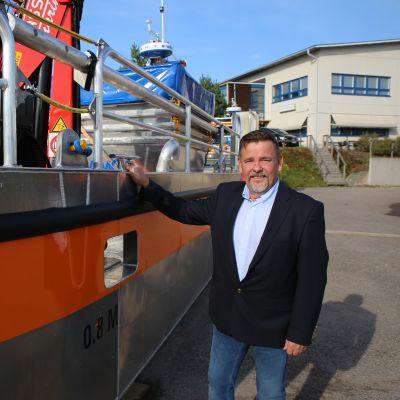 Lamor oy:n varatoimitusjohtaja Juha Muhonen ja öljyntorjunta-alus, joka on lähdössä Grönlantiin.