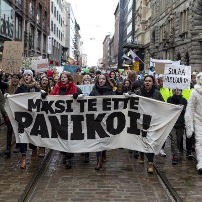 """Unga demonstrerar, plakat med texten """"Varför panikerar ni inte"""". En demonstrant i isbjörnsdräkt. Centrum av Helsingfors."""