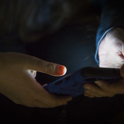 anonyymi henkilö pitää puhelinta kädessä