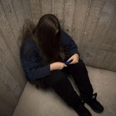 anonyymi henkilö istuu nurkassa ja pitää puhelinta kädessä