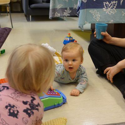 Två barn i krypåldern tittar på varandra,en förälder sitter på golvet med benen i kors och en kaffemugg i handen.