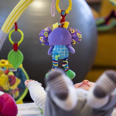 lapsi makaa lattialla lelujen keskellä