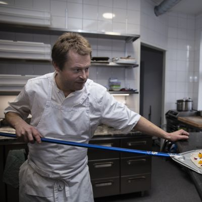 Restaurangägare Nick Victorzon skyfflar in en pizza i ugnen.