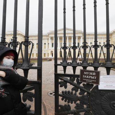 Hengityssuojaa käyttävä nainen käveli keskiviikkona Pietarissa suljetun Venäläisen taiteen museon portin ohitse.