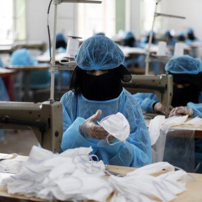 Nainen valmistaa hengityssuojainta Jemenin pääkaupungissa Sanaassa 13.4.2020.