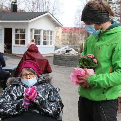 hoivakodissa asuva Elvi Lahti ja lapsenlapsensa Markus Kumpula palvelukoti Aarnenpihan pihalla