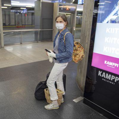 Nainen odottaa bussia Kampin metroasemalla.