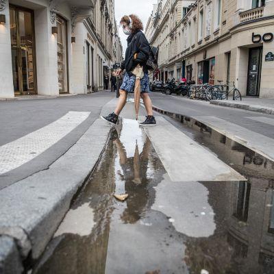 nainen ylittää suojatietä Pariisissa suojain kasvoillaan