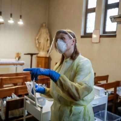 En sjukskötare i skyddsutrustning inne i kyrka