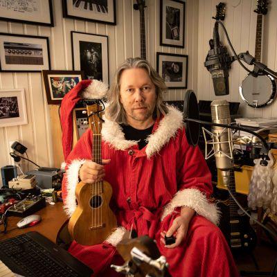 Kuopion yliopistollisen sairaalan ylilääkäri Tatu Kemppainen joulupukiksi pukeutuneena kitara kädessä.