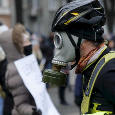 Närbild på en man med gasmask och cykelhjälm.
