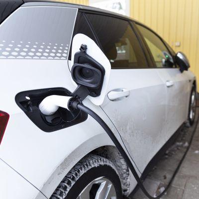 Sähköauto latauksessa omakotitalon autokatoksessa.