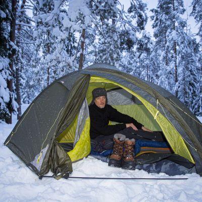 Mies majoittuu teltassa talvella.